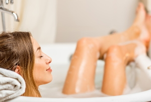 woman reclining in a bubble bath in a small, well lit bathroom with candles