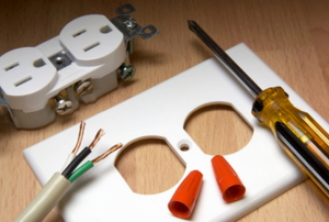 A disassembled electrical outlet with wiring, a screwdriver, face plate, caps, the outlet itself.