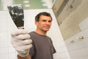 Man in a bathroom holding up a scraper.