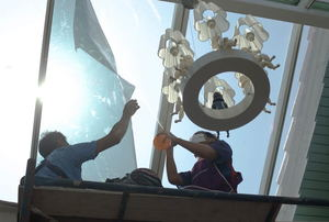 A pair of workers installing window film on windows.