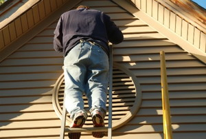 Man on a ladder leaning against vinyl siding on a tan house.