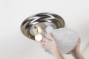 A woman installs a light fixture.