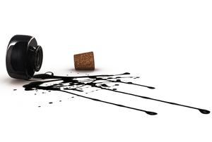 A splatter of black ink spilled from an ink bottle.