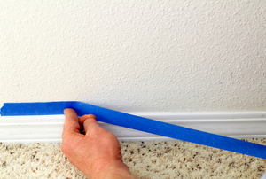 A DIY-er applying painter's tape.