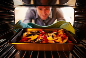 A tray of roasting vegetables being put in the oven.