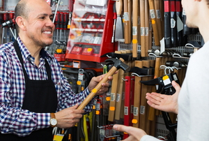 salesman showing a hammer to a customer
