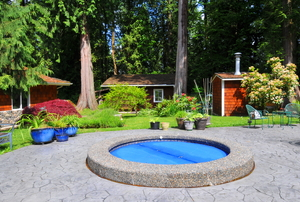 A backyard patio with a small hot tub set in the ground.
