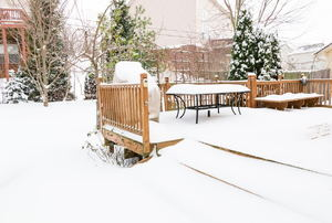 A snow-covered backyard and deck.