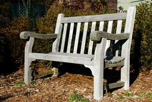 A worn outdoor bench with exposed wood.
