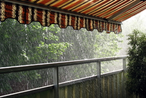 Rain pours off of an attached awning covering a deck.