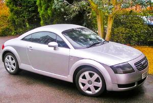 A grey car in a driveway.