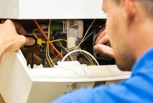 A man repairs a heater.