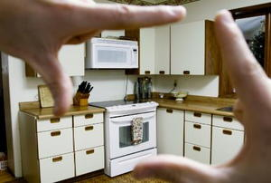 Person sizing up an outdated kitchen for a renovation.