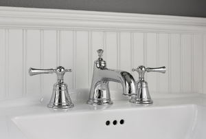 A sink with silver faucet and beadboard.
