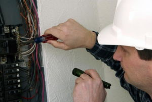 A man inspects a circuit breaker.