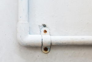 A pipe attached to a wall with pipe straps.