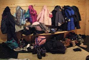 A messy, cluttered mudroom, filled with shoes, bags, and jackets.