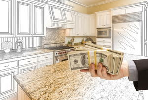 Hand holding cash in front of a kitchen remodel plan