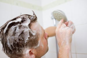 A man taking a shower and looking at the shower head in confusion.