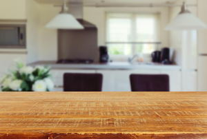 A closeup of a wood kitchen counter with a kitchen in the background.
