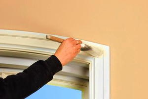 A person painting window trim with white paint.
