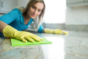 woman cleaning a stone countertop