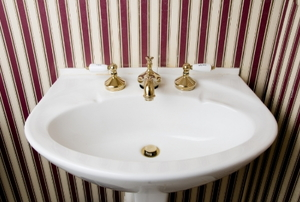 White porcelain sink in a bathroom with red striped wallpaper.