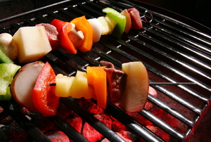 Skewers cooking on a stainless steel grill grate.