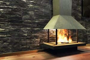 free standing metal fireplace in front of stone wall