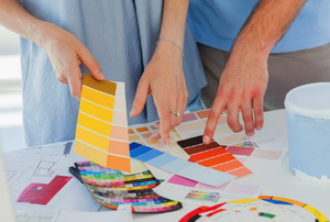 A couple sorting through various colored paint chips