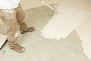 A professional painter uses a roller to spread white paint over a concrete floor.