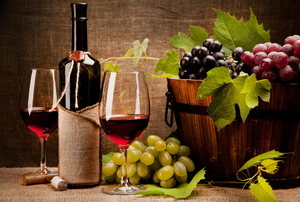 Two wine glasses and a bottle of red wine sit beside a bucket of grapes.