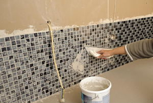 Someone grouting a tile backsplash.