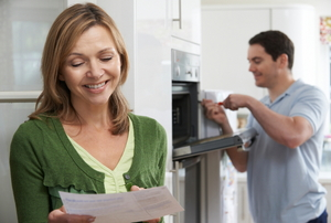 A woman holding a paper while a man works in the background on an oven in a kitchen.