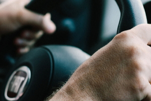 hands gripping steering wheel while driving car