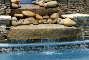 A waterfall water feature with rocks.