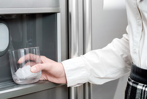 A woman uses an ice maker.