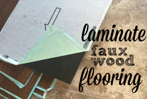 "Laminate flooring planks with the words ""laminate faux wood flooring."""