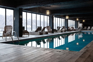an indoor pool surrounded by windows