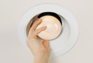 A person screwing in a bulb to a recessed lighting fixture.