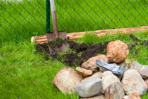 Stones and tools stand by for building a flowerbed border.