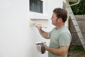 Man touching up paint on outside of a home
