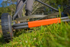 Close-up of push reel mower cutting grass.