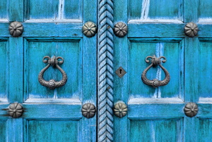 Decorative doorknobs on a blue door.