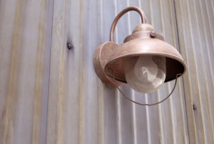 A copper light fixture mounted to the side of a building