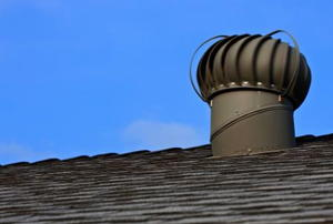 A mushroom-shaped gable vent against a blue sky.
