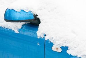 A blue car engulfed in snow.