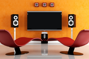 modern room with curvy chairs and speakers around a television