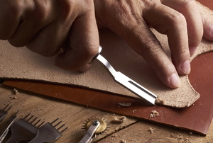 hands cutting leather with a special curved tool