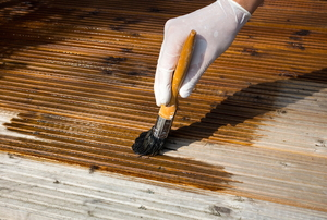 Wearing rubber gloves and applying deck stain with a brush.